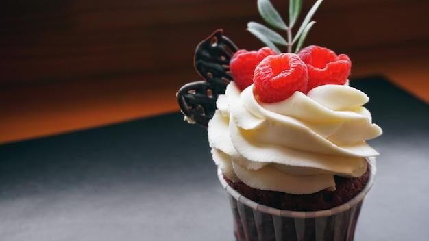 暗い背景のおいしいラズベリーカップケーキ-手作りの甘いデザート、バタークリームとラズベリーのカップケーキ