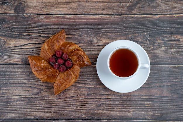 Delicious raspberry pastry with a cup of black tea placed on a wooden table .