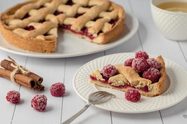 Delicious raspberry pie on white wooden table