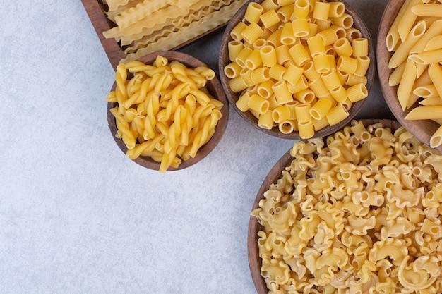 Вкусные сырые макароны и вермишель на деревянных мисках