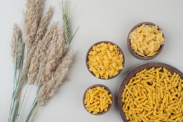 Вкусные сырые макароны на деревянной тарелке