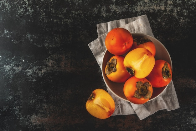 Delicious raw ripe persimmon fruit on dark rusty metal background top view