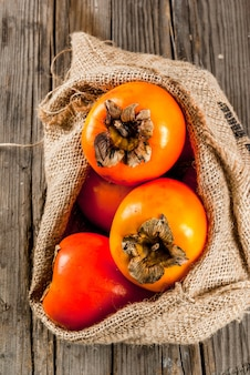 Delicious raw ripe persimmon fruit on old wooden background