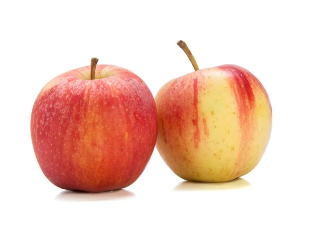 白いスペースにおいしい赤と黄色のリンゴ