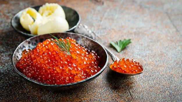 Delicious red caviar in black bowl.