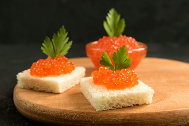 Delicious red caviar on wheat bread served with parseley on wooden desk.