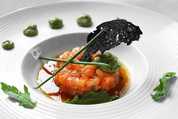하얀 접시에 소스를 곁들인 맛있는 붉은 생선
