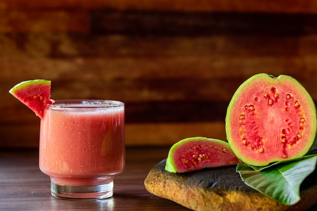 Delicious red guava juice alongside a slice of guava with guavas and leaves on rustic wood