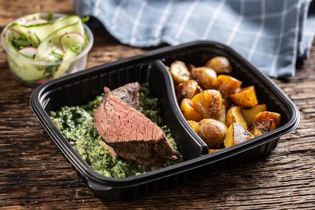 Вкусный стейк из красного мяса sous vide, упакованный в переносную пластиковую коробку на вынос, подается с хрустящим жареным картофелем, пикантным соусом из шпината и салатом из свежих овощей.