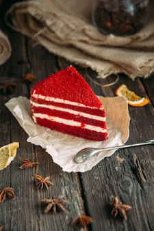 Delicious red velvet cake on a wooden table with spoon