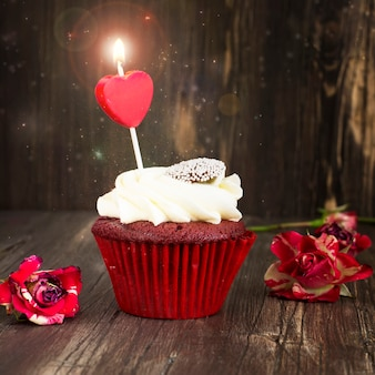 Delicious red velvet cupcake with burning candle