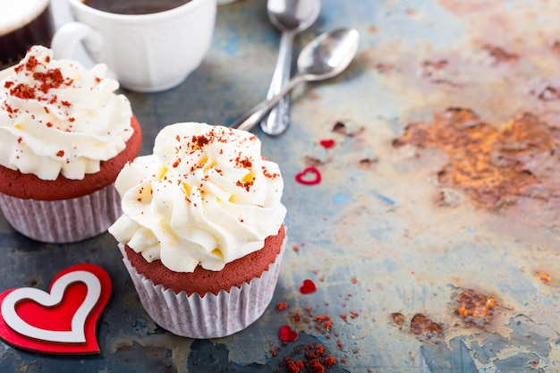 Delicious red velvet cupcakes for valentines day on rusty old metal surface. holiday food concept. copy space
