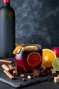 Восхитительное красное вино со специями. глинтвейн и ингредиенты на темном столе
