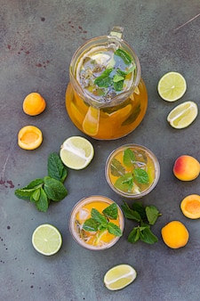 Delicious refreshing drink with apricot, lime and mint in jug and glasses.