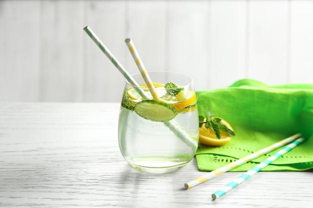 Вкусная освежающая вода с огурцом в стакане на столе