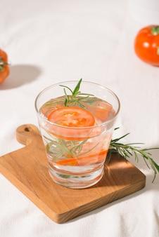 테이블에 유리에 로즈마리와 토마토와 맛있는 상쾌한 물