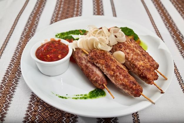 Восхитительная ресторанная закуска к пиву и крепким алкоголям: обжаренная колбаса с томатно-зеленым соусом и кусочками лука. стол накрыт вышитой скатертью.