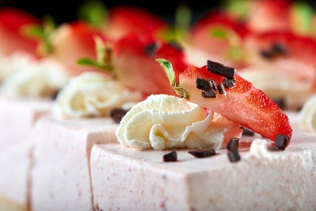 おいしいレストランのデザート:新鮮なイチゴ、すりおろしたチョコレート、ホイップクリームで装飾された甘いスフレ。軽いワインとシャンパンの前菜。