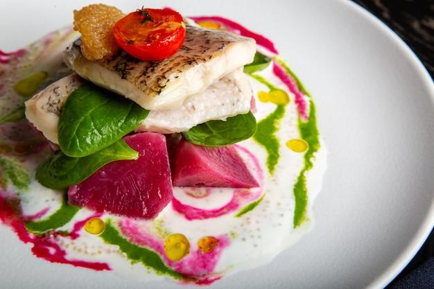 レストランのソースの下で白身魚、カワカマス、スズキの野菜のおいしいレストラン料理。大きな白いプレートのクローズアップの健康的な高級食品