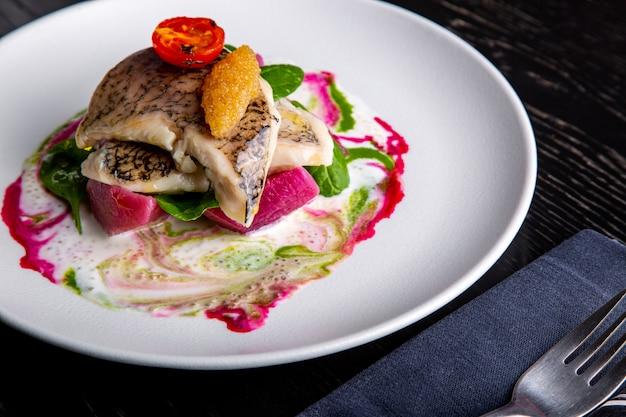 Вкусное ресторанное блюдо из белой рыбы, щуки, морского окуня с овощами под соусом в ресторане