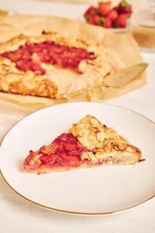 Deliziosa torta gallate di fragole al rabarbaro con ingredienti su un tavolo bianco
