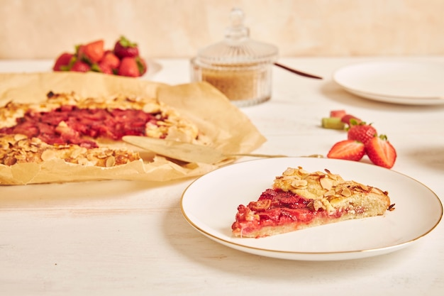 Delicious rhubarb strawberries gallate cake with ingredients on a white table