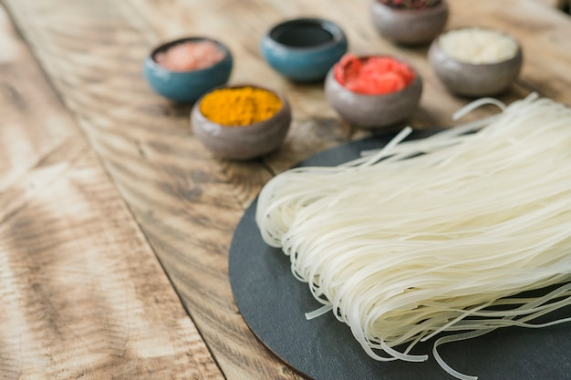 Delicious rice noodles and ingredients in bowl on old wooden texture plank