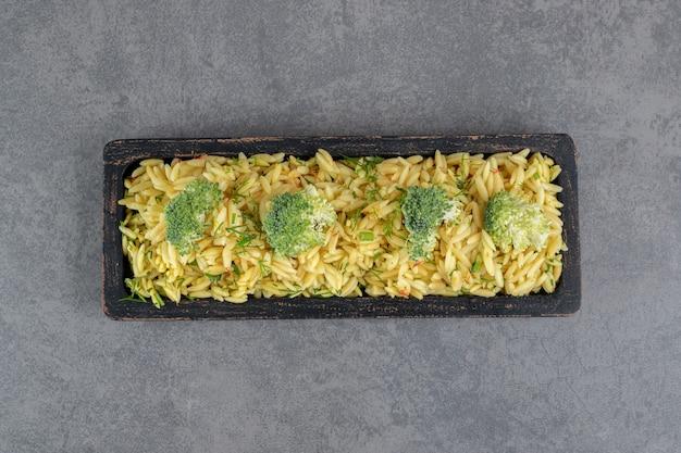 Вкусный рис с брокколи на черной тарелке. фото высокого качества