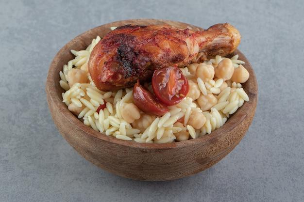나무 그릇에 병아리콩과 닭 다리를 넣은 맛있는 쌀.