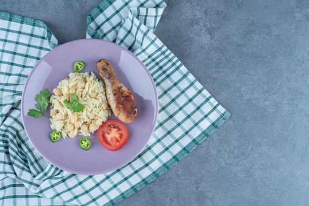 Вкусный рис с нутом и голенью на фиолетовой тарелке.