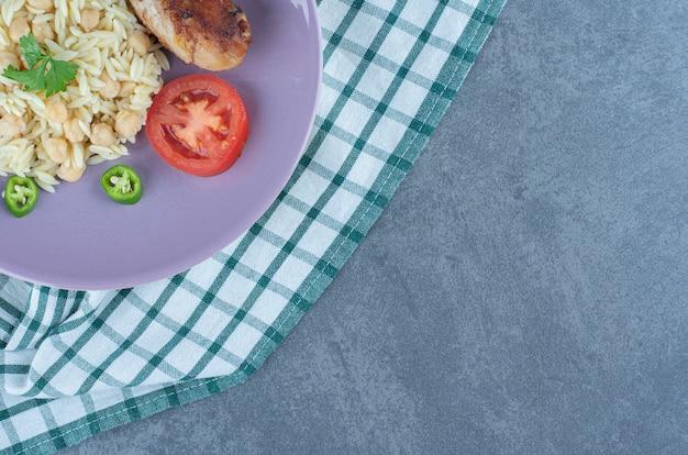 Вкусный рис с нутом и голенью на фиолетовой тарелке. Бесплатные Фотографии
