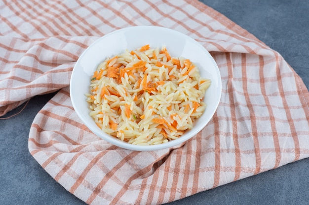 Delicious rice with chopped carrots in white bowl.