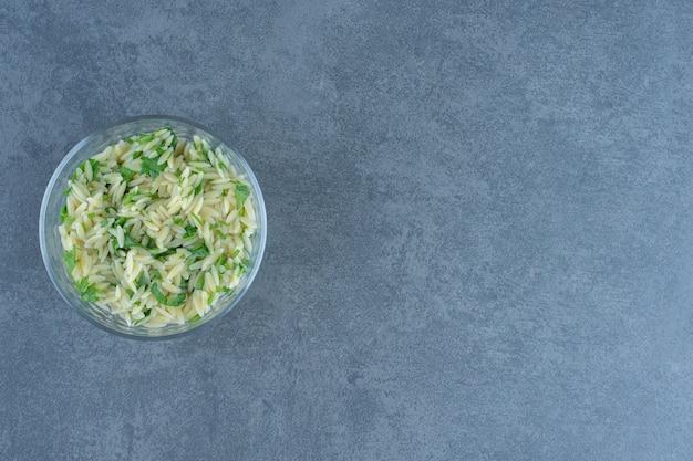 Вкусный рис с зеленью в стеклянной миске.
