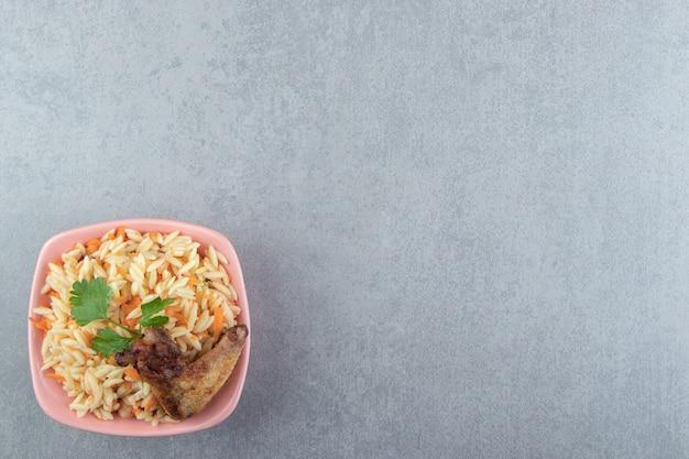Вкусный рис с жареным крылышком в розовой миске.