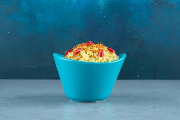 Вкусный рис с ломтиками помидора в синей миске.