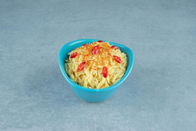 青いボウルにトマトのスライスが入ったおいしいご飯。