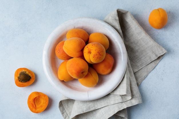 Delicious ripe apricots on a light concrete