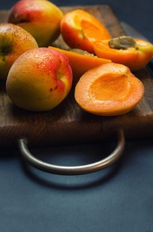 Delicious ripe apricots on wooden cutting board