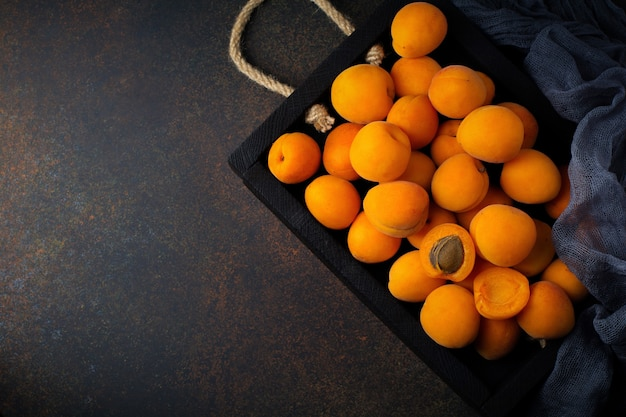Delicious ripe apricots on a wooden stand