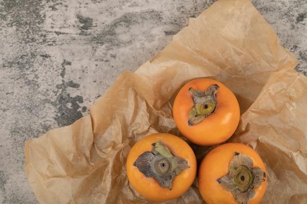 紙に載せた美味しい熟した富有果実