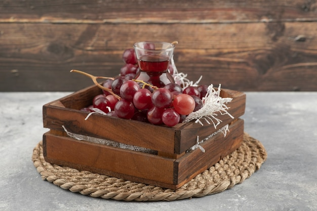 Delicious ripe grapes and glass of juice in wooden box.