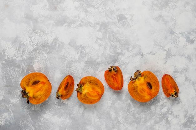 Delicious ripe persimmon fruit on concrete
