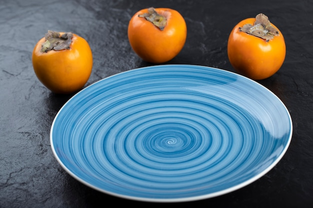 Delicious ripe persimmon fruits and empty blue plate on black surface.