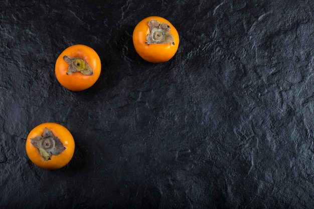 Delicious ripe persimmon fruits placed on black surface.