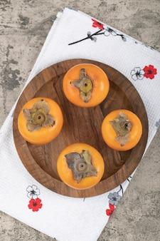 木の板の上に置かれたおいしい熟した柿の果実