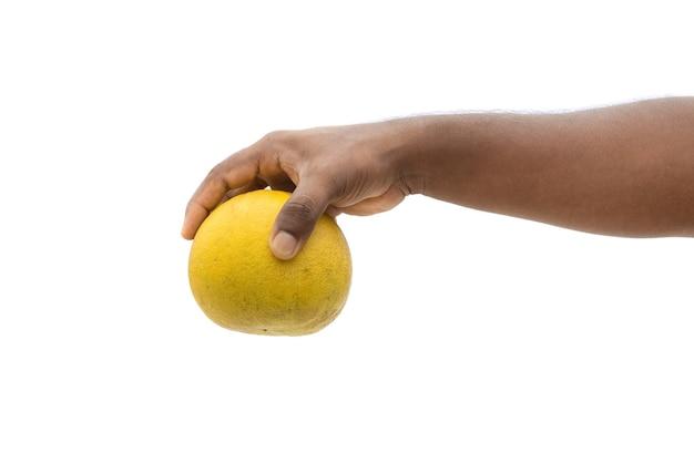 白い背景で隔離の手で保持しているおいしい熟したザボン果実