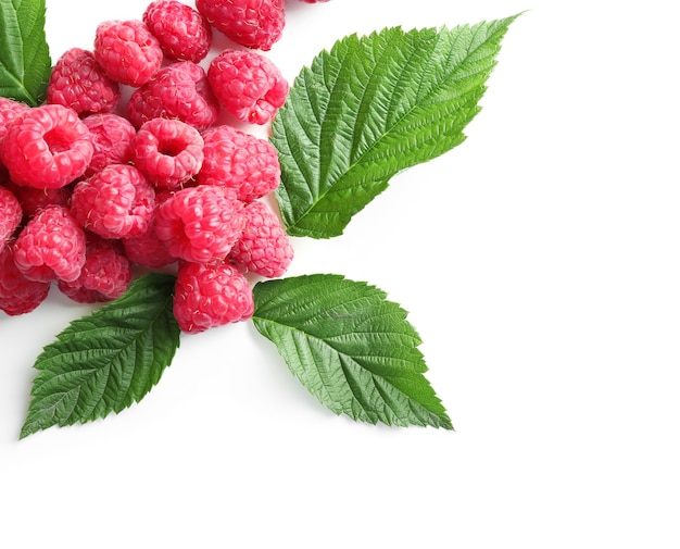 Delicious ripe raspberries with leaves on white background