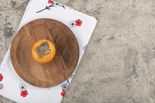 木の板の上に置かれたおいしい熟した単一の柿