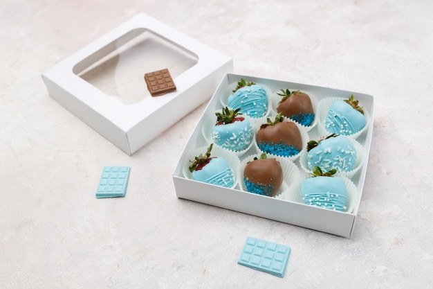 Delicious ripe strawberries in brown and blue chocolate packed in a gift box