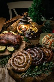 リンゴ、自家製ソーセージ、サラダ、クリスマスケーキを添えたおいしいローストクリスマスアヒル